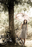 Beautiful girl near bike.. Beautiful girl with umbrella near bike and tree at rest in forest. Photo in retro style Stock Images