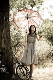 Beautiful girl near bike.. Beautiful girl with umbrella near bike and tree at rest in forest. Photo in retro style Stock Image