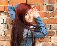 Beautiful girl near brick wall, smiling Royalty Free Stock Photography