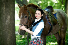 Beautiful girl near brown horse. Pinto with a spot. Forest, bright light, professional photo. Looks like film or fairy tail, cosplay. white blouse, denim Royalty Free Stock Photos