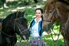 Beautiful girl near brown horse. Pinto with a spot. Forest, bright light, professional photo. Looks like film or fairy tail, cosplay. white blouse, denim Stock Images