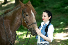 Beautiful girl near brown horse. Pinto with a spot. Forest, bright light, professional photo. Looks like film or fairy tail, cosplay. white blouse, denim Royalty Free Stock Photography