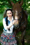 Beautiful girl near brown horse. Pinto with a spot. Forest, bright light, professional photo. Looks like film or fairy tail, cosplay. white blouse, denim Royalty Free Stock Images