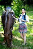 Beautiful girl near brown horse. Pinto with a spot. Forest, bright light, professional photo. Looks like film or fairy tail, cosplay. white blouse, denim Stock Image