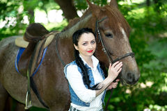 Beautiful girl near brown horse. Pinto with a spot. Forest, bright light, professional photo. Looks like film or fairy tail, cosplay. white blouse, denim Stock Photography