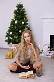 Beautiful girl near a Christmas tree in the room royalty free stock photos