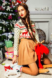 Beautiful girl near a Christmas tree sitting on a toy deer. A lo royalty free stock photography
