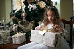 Beautiful girl near Christmas tree unpacking presents Royalty Free Stock Photography