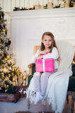 Beautiful girl near Christmas tree unpacking presents sitting on a chair Stock Photo