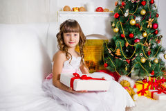 Beautiful girl near the decorated Christmas tree, holds a white Royalty Free Stock Photo