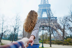 Beautiful girl near the Eiffel tower, follow me concept Royalty Free Stock Image
