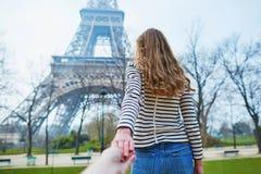 Beautiful girl near the Eiffel tower, follow me concept Stock Photos