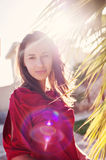 Beautiful girl near the palm trees and sun backlit Royalty Free Stock Photos