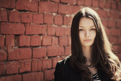 Beautiful girl near red brick wall Royalty Free Stock Image