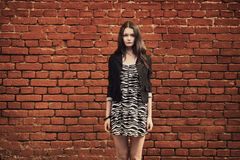 Beautiful girl near red brick wall Stock Photos