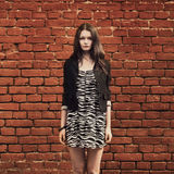 Beautiful girl near red brick wall Royalty Free Stock Photos