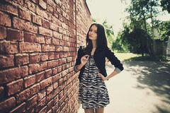 Beautiful girl near red brick wall Stock Image