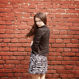 Beautiful girl near red brick wall Royalty Free Stock Photography