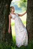 Beautiful girl near tree. Beautiful girl in a long dress with a bright trunks of large trees Royalty Free Stock Photo