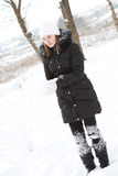 Beautiful girl near a tree in snow Royalty Free Stock Image