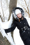 Beautiful girl near a tree in snow Royalty Free Stock Images