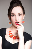 Beautiful girl in a necklace. finger  his mouth. touching her lip Stock Photography