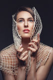 Beautiful girl with net. Beautiful young woman with rough net. Natural makeup. Fashion beauty shot over dark background Stock Images