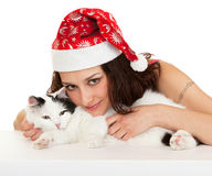 Beautiful girl in a New Year hat with a cat. Royalty Free Stock Image