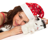 Beautiful girl in a New Year hat with a cat. Royalty Free Stock Images