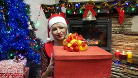 Beautiful girl in New Year`s clothing and Christmas hat. Woman open a gift in a red box with a bow near xmas tree and fireplace. blonde girl have gift box with stock video