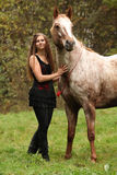 Beautiful girl with nice dress standing next to nice horse Stock Photos