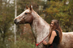 Beautiful girl with nice dress standing next to nice horse Royalty Free Stock Photo