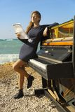 Beautiful girl with notes from an old piano on the Royalty Free Stock Photo