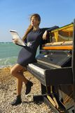 Beautiful girl with notes from an old piano on the Royalty Free Stock Image