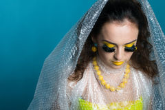 Beautiful girl with odd make-up. Young beautiful woman with creative make-up in plastic bag clothes Royalty Free Stock Image
