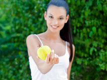 Beautiful girl offering a yellow apple. Attractive brunette girl offering a delicious yellow apple. Blur on the girl, focus on the apple. Outdoors Royalty Free Stock Images