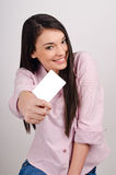 Young woman smiling holding a blank business card. Beautiful girl offering you a visit card Stock Photos