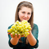 Beautiful girl offers grapes Stock Images