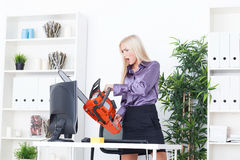 Beautiful girl at the office cuts the monitor with a chainsaw Stock Photo