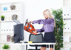 Beautiful girl at the office cuts the monitor with a chainsaw Stock Image