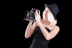 The beautiful girl with the old camera. The beautiful fair-haired girl with the old camera on a black background, isolation Royalty Free Stock Photo