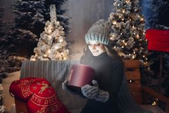 Beautiful girl opening magic box with present at Christmas night. Beautiful girl in gray hat sitting on bench among many Christmas trees holding and opening royalty free stock image