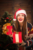 Beautiful girl opening a present near New Year tree. Beautiful girl opening a present and laughing with excitement near New Year tree. Happy lady with red lips Royalty Free Stock Photo