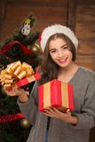 Beautiful girl opening a present near New Year tree. Portrait of beautiful and attractive girl opening a present near New Year tree. Smiling lady spending Royalty Free Stock Image