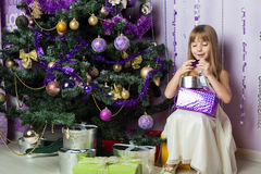 The beautiful girl opens a Christmas present Stock Image