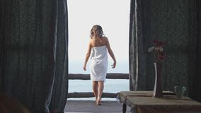 Beautiful girl opens curtains walks to sea view terrace. Young woman waking up stretches hands looking at ocean stock video footage