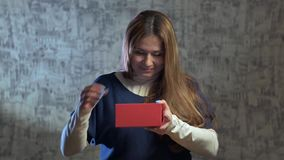 Beautiful girl opens a gift. Shakes the red gift box and opens it and takes the phone in the white box stock video footage