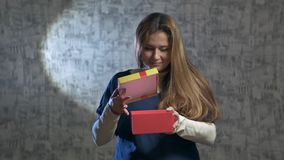 Beautiful girl opens a red gift. Slow. beautiful girl opens a gift. She shakes the red gift box and opens it and pulls out a jewel case stock footage