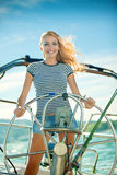 The beautiful girl operates the yacht Royalty Free Stock Photos