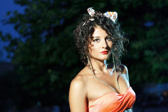 Beautiful girl with orange bra. Beautiful girl in orange bra long golden chain earings and curly hair at night in park Stock Images